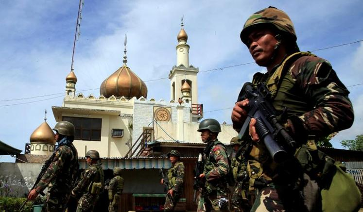 Soldati filippini marciano davanti a una moschea di Marawi